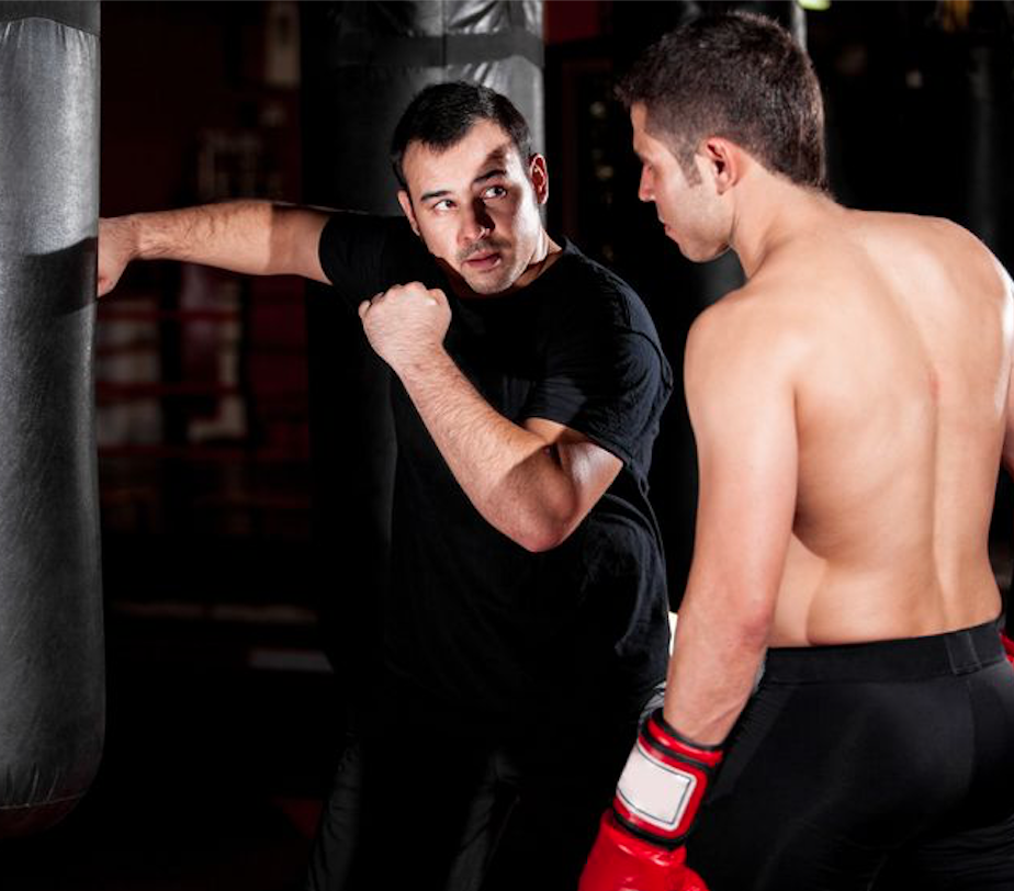 Boxer and his coach practicing some moves on a punching bag at a gym