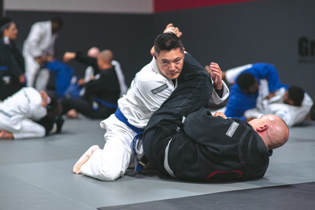 Two men sparring on the floor wearing martial arts uniforms