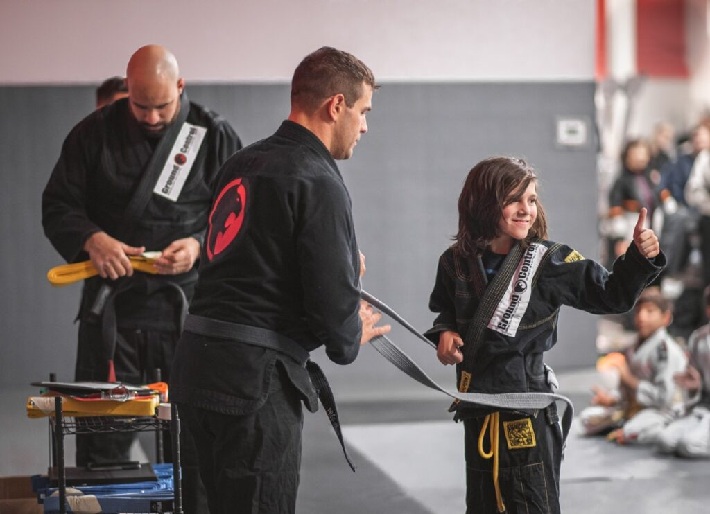 Martial arts instructor awarding a kid with his new belt