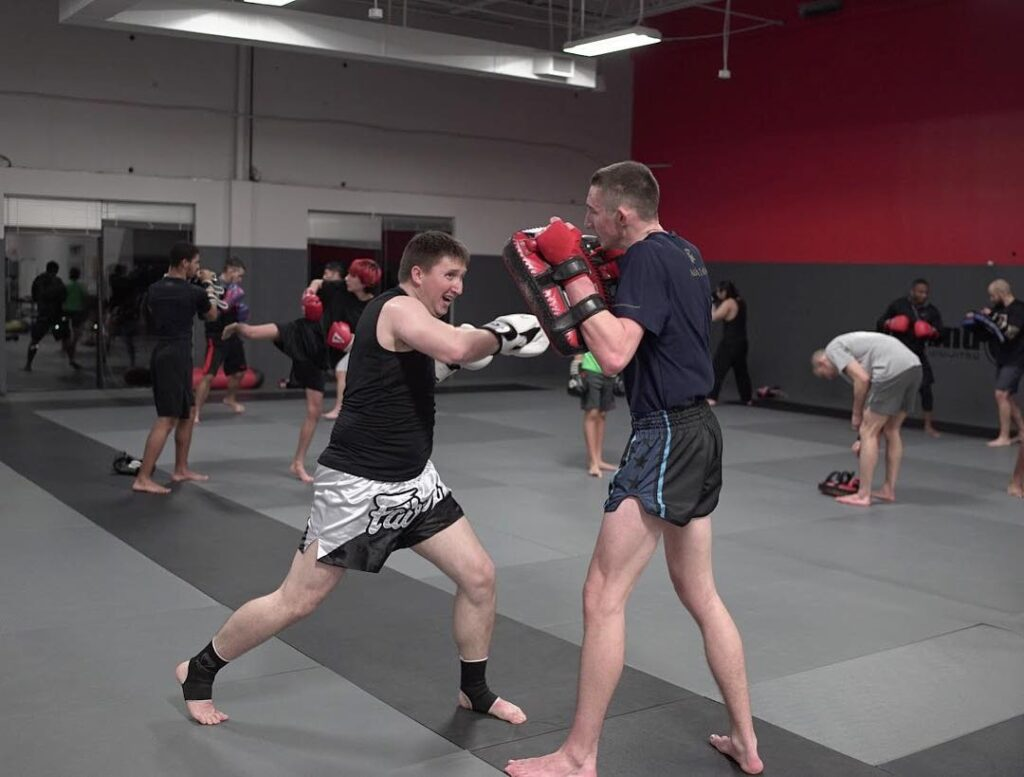 Martial arts student practicing punching on strike pads