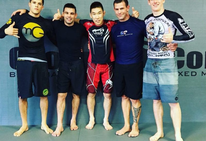 Five men posing and smiling in a martial arts facility