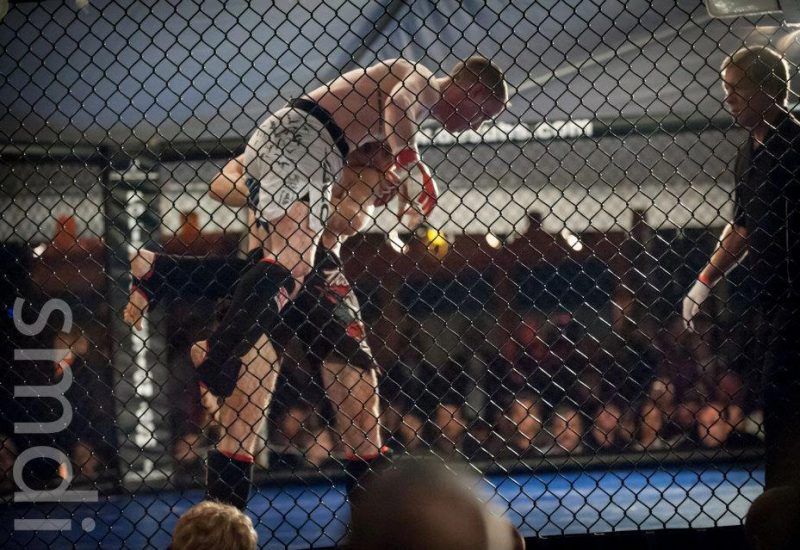 Man lifting another man in an MMA ring surrounded by chain link fencing