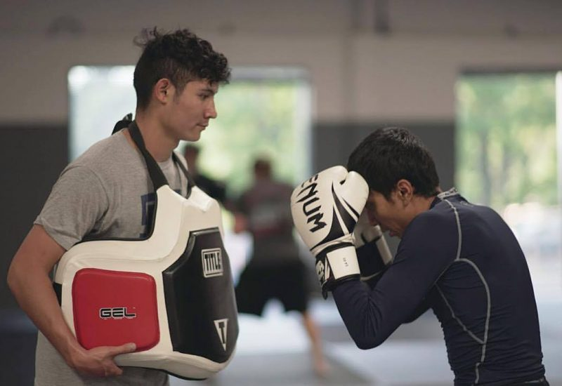 Man practicing punching with trainer